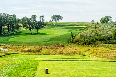 Hole 12 preview image showing tee box in the foreground and rolling hills and trees along the green in the background.