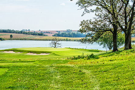 Hole 14 preview shows green with sand traps in the foreground and natural rolling Iowa hills in the background, separted by a body of water.